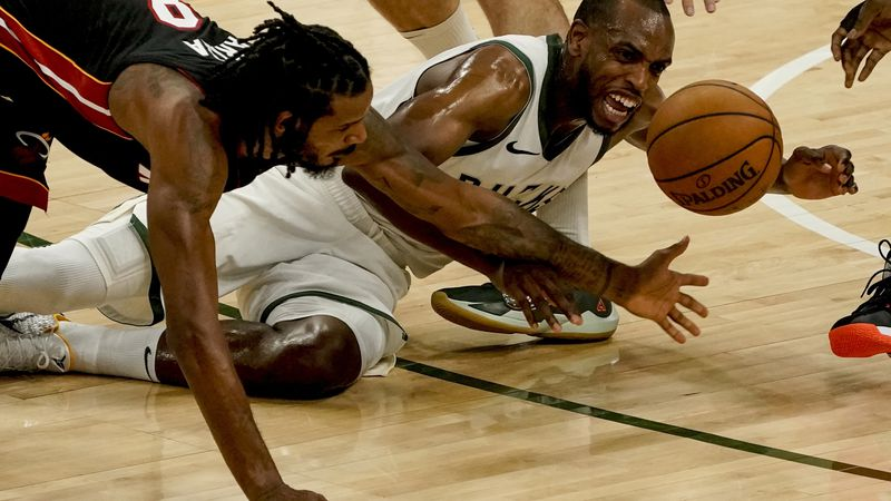 Miami Heat's Trevor Ariza and Milwaukee Bucks' Khris Middleton go after a loose ball during the...