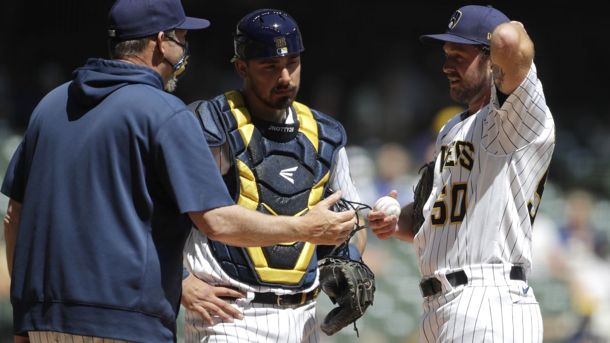 Milwaukee Brewers' Alec Bettinger (50) talks with pitching coach Chris Hook, left, during the...