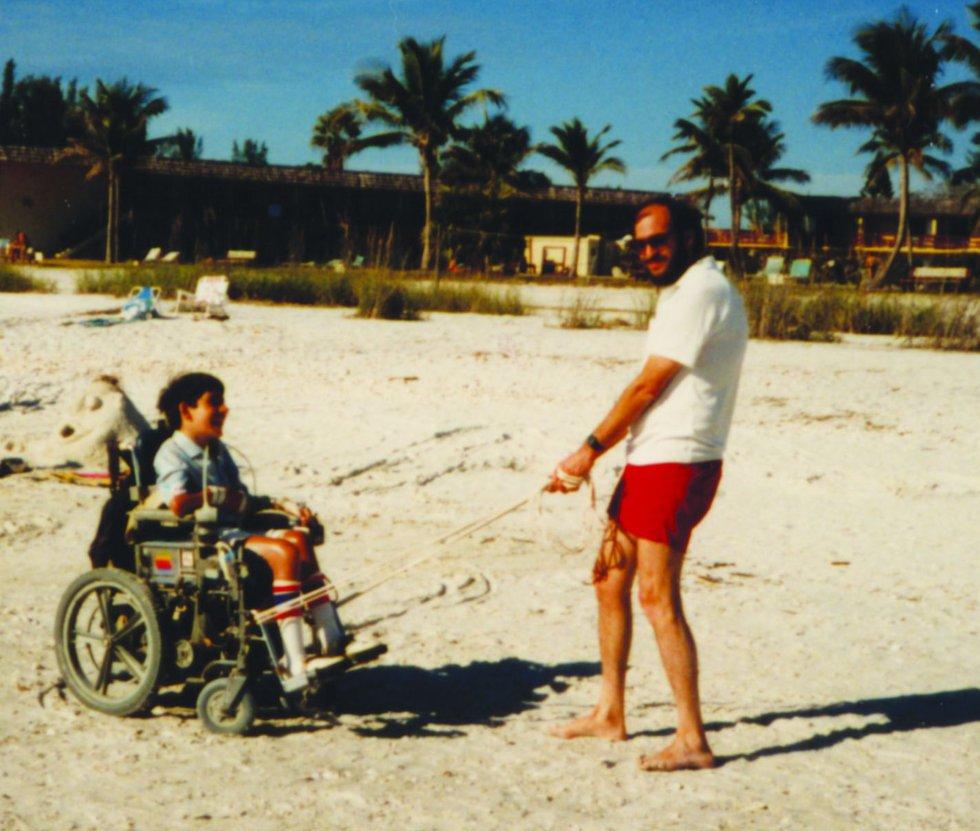 Howie Erlanger pulls Jeff's wheelchair across a sandy beach.