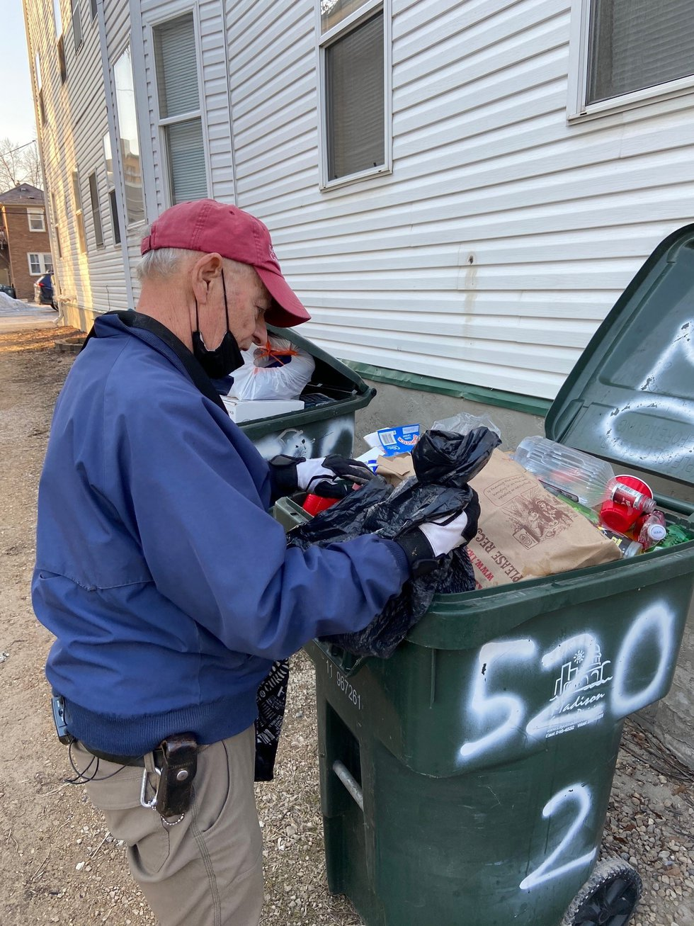 Gary Gates removes garbage from a recycle bin