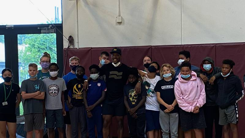 """Elijah """"EZ"""" Muhammad poses with youth at Madison's Goodman Center following a workout"""