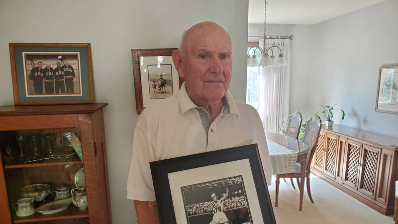 John Bennett holds a photo of him competing in the 1956 Olympic games