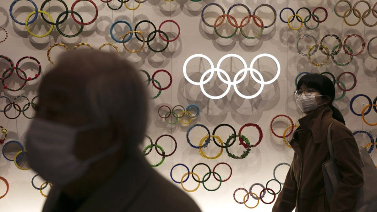 Two people wear masks as they visit the newly opened Japan Olympic Museum located near the New...