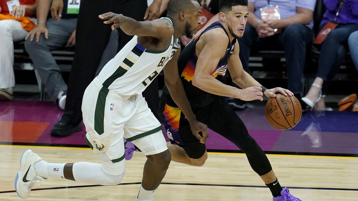 Phoenix Suns guard Devin Booker, right, dribbles against Milwaukee Bucks forward Khris...