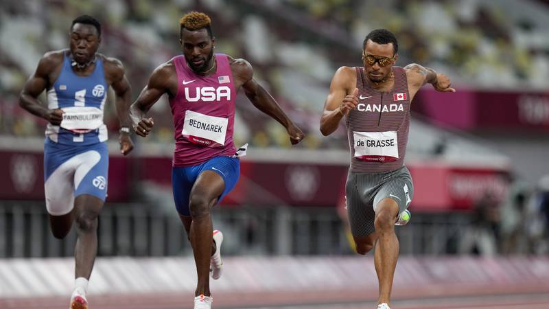 Andre De Grasse, right, of Canada, wins the men's 200-meter final at the 2020 Summer Olympics,...
