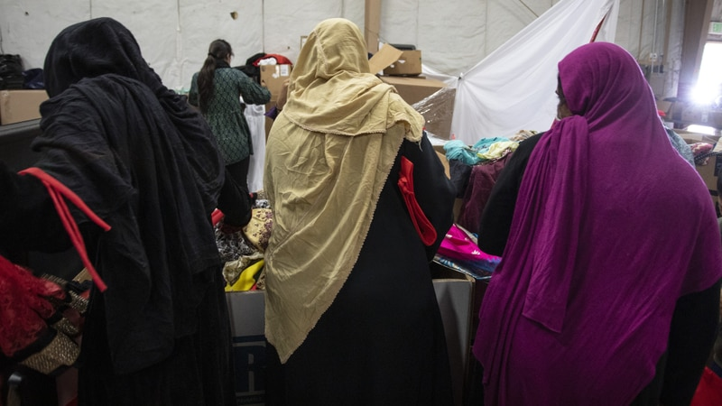 Afghan refugees look for donated clothing and shoes at the donation center at the Fort McCoy...