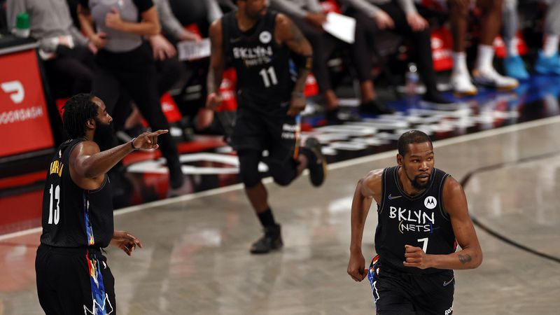 Brooklyn Nets guard James Harden (13), forward Kevin Durant (7) and guard Kyrie Irving (11) run...