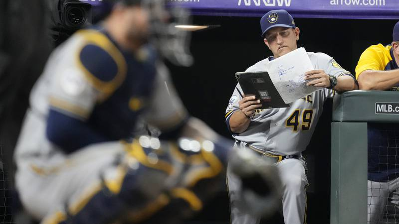 FILE - In this June 19, 2021, file photo, Milwaukee Brewers hitting coach Andy Haines studies...