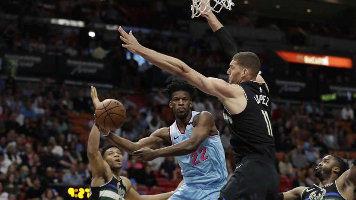 Miami Heat forward Jimmy Butler (22) passes the ball around Milwaukee Bucks center Brook Lopez (11) and forward Giannis Antetokounmpo (34) during the first half of an NBA basketball game, Monday, March 2, 2020, in Miami. (AP Photo/Wilfredo Lee)