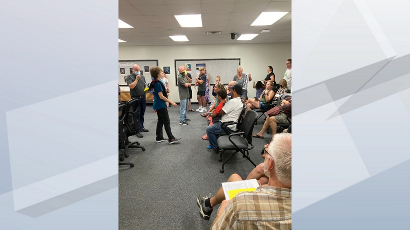 Protesters against mask wearing in Oshkosh Schools enter a school board meeting.