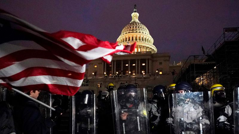 Police stand outside the Capitol after a day of rioting protesters, Wednesday, Jan. 6, 2021, at...
