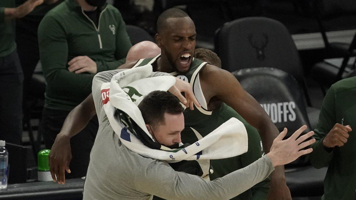 Milwaukee Bucks' Khris Middleton celebrates with teammate Pat Connaughton after making a basket...