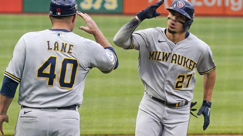 Milwaukee Brewers' Willy Adames (27) rounds third to greetings from coach Jason Lane (40) after...