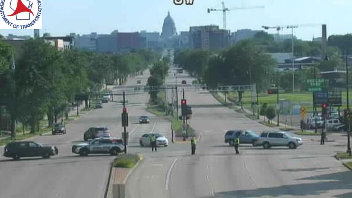 A WisDOT camera shows MPD squad cars barricading lanes along East Washington Avenue.