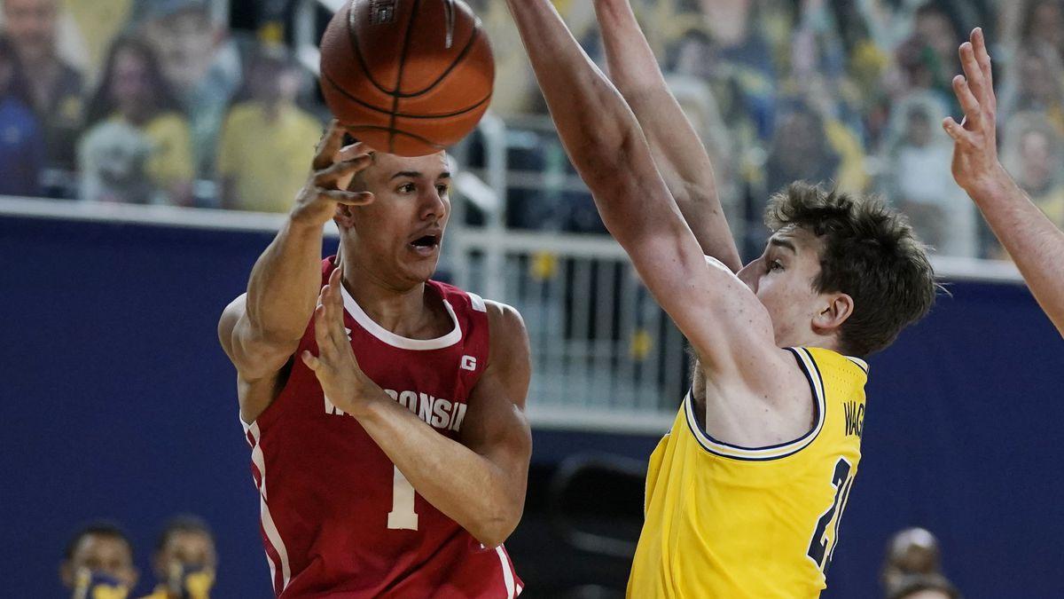Wisconsin guard Jonathan Davis (1) passes the ball around Michigan guard Franz Wagner (21)...