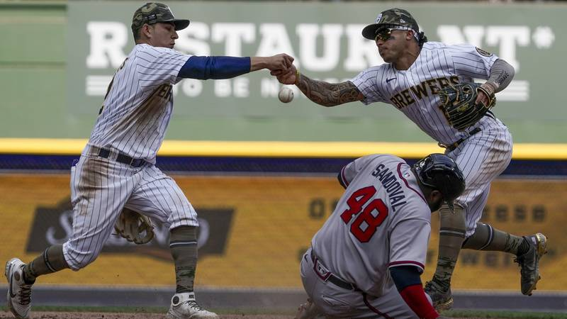 Milwaukee Brewers' Kolten Wong and Luis Urias fumble the ball as Atlanta Braves' Pablo Sandoval...