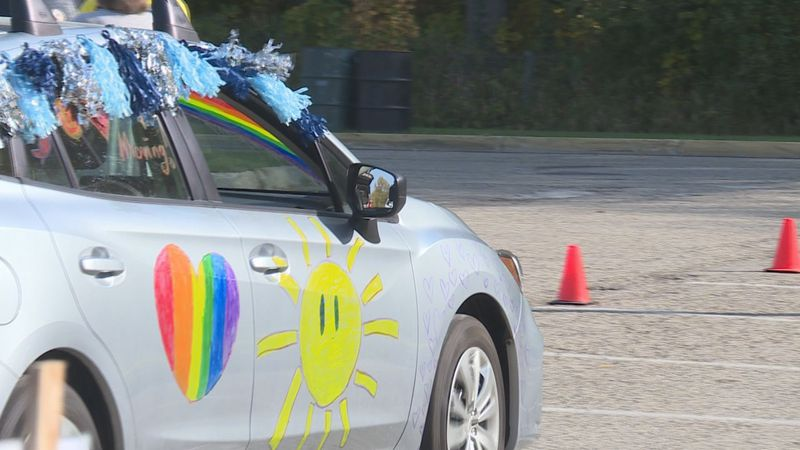 A car, decorated in support of NAMIWalks, drives by the event in Madison.