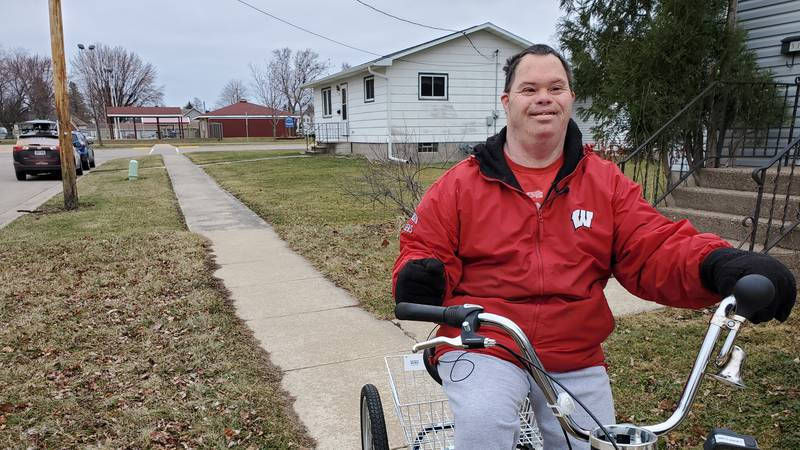 Koca hops on his tricycle and rides house to house returning his neighbor's empty garbage cans...