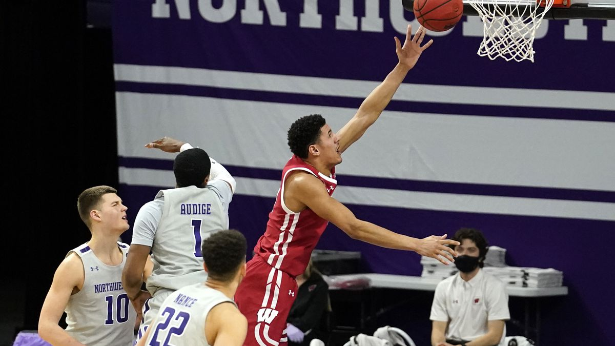 Wisconsin guard Jonathan Davis, right, drives to the basket past Northwestern forward Miller...
