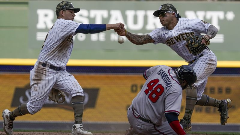 Milwaukee Brewers' Kolten Wong and Luis Urias fumble the ball as Atlanta Braves' Pablo Sandoval...