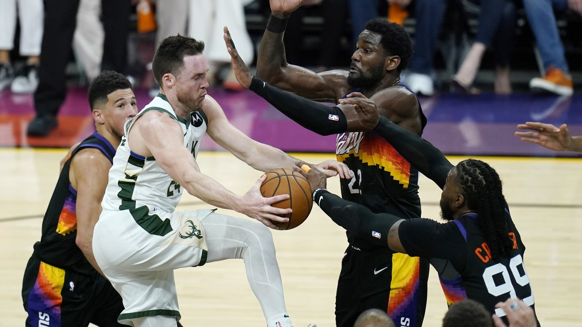 Milwaukee Bucks guard Pat Connaughton, front left, gets stopped by Phoenix Suns guard Devin...