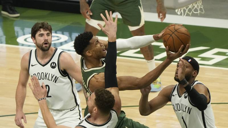 Milwaukee Bucks' Giannis Antetokounmpo shoots past Brooklyn Nets' Bruce Brown and Blake Griffin...