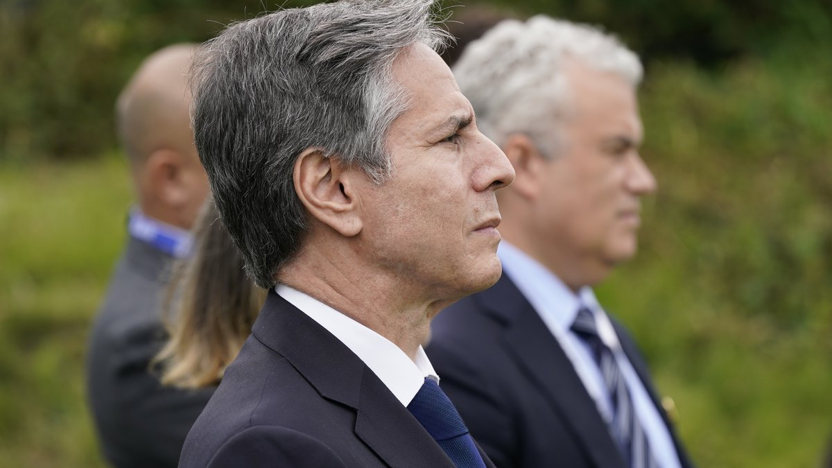 Secretary of State Antony Blinken listens as President Joe Biden speaks about his...