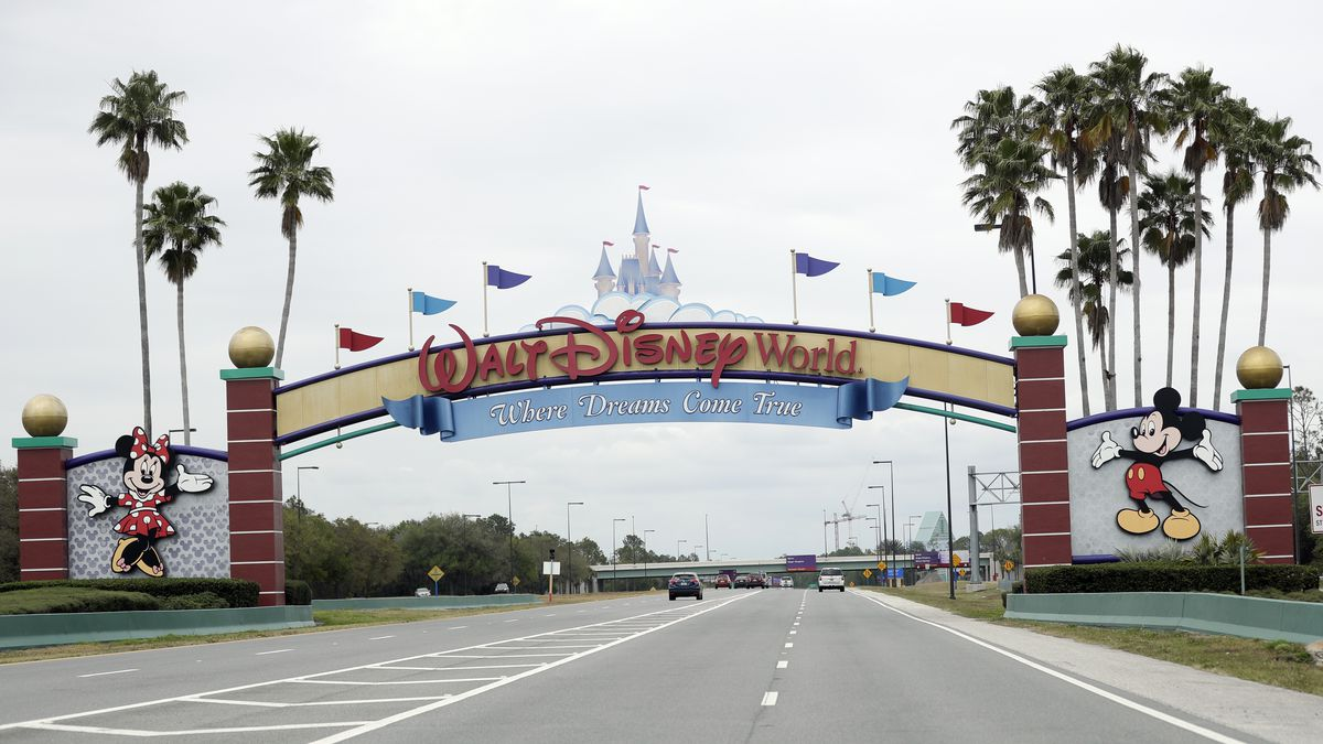 FILE - In this Monday, March 16, 2020, file photo, the road to the entrance of Walt Disney World has few cars, in Lake Buena Vista, Fla.