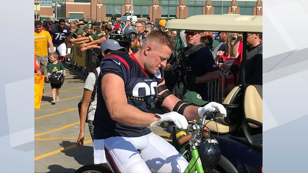 Houston Texans JJ Watt, a Wisconsin native, rides a child's bike outside Lambeau Field during a joint Packers-Texans training camp, joining in a Green Bay Packers tradition Watt himself watched as a kid (WBAY photo)