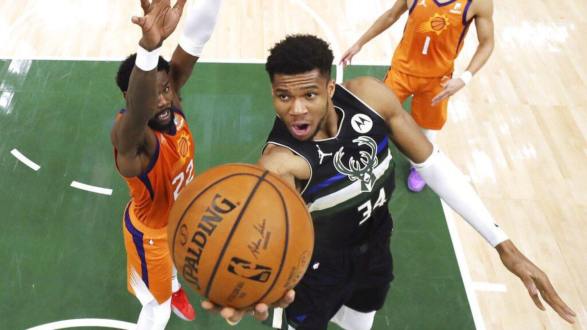 Milwaukee Bucks' Giannis Antetokounmpo shoots next to Phoenix Suns' Deandre Ayton, left, during...