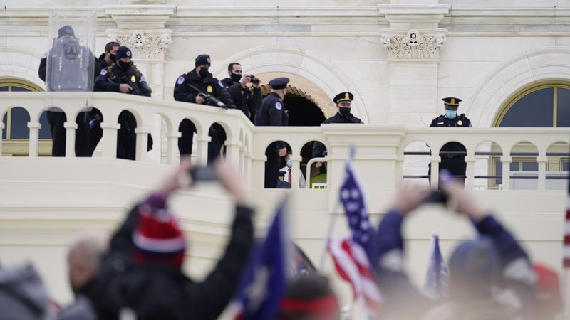 Police keep a watch on demonstrators who tried to break through a police barrier, Wednesday,...