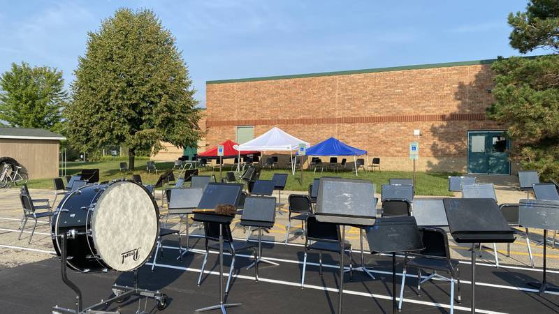 Chairs and music stands fill part of Patrick Marsh Middle School's back parking lot for outdoor...
