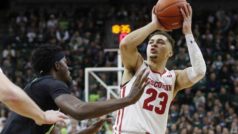 Wisconsin guard Kobe King (23) shoots over the defense of Michigan State forward Gabe Brown...