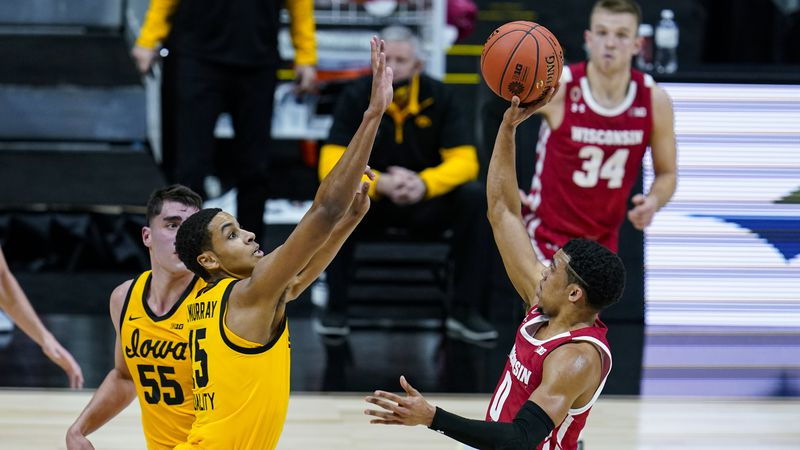 Wisconsin guard D'Mitrik Trice (0) shoots over Iowa forward Keegan Murray (15) in the first...