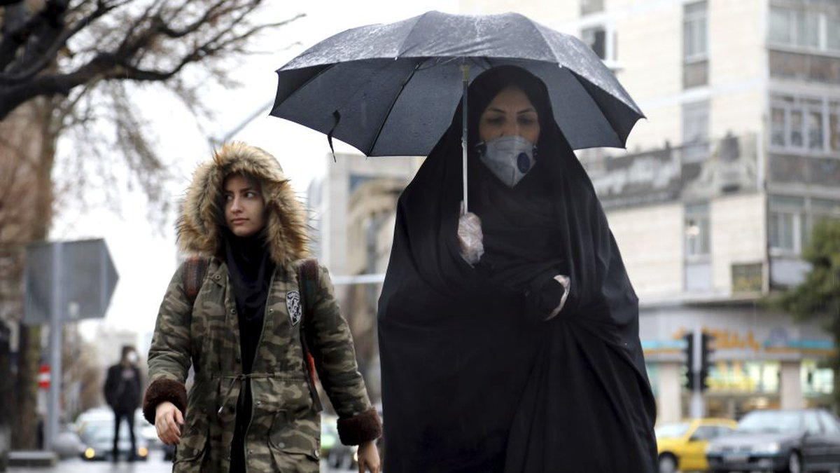 A pedestrian wears a mask and gloves to help guard against the Coronavirus in downtown Tehran,...