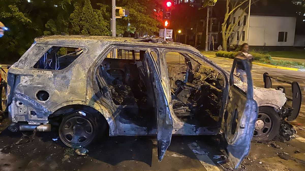 A Madison Police Dept. cruiser sits burnt after the first night of protests in downtown...