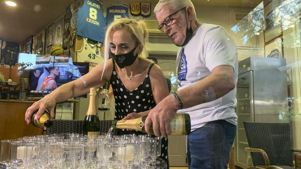 Coffee shop owner Yiannis Tzikas and his wife Kaiti Drimba pour champagne into plastic glasses...