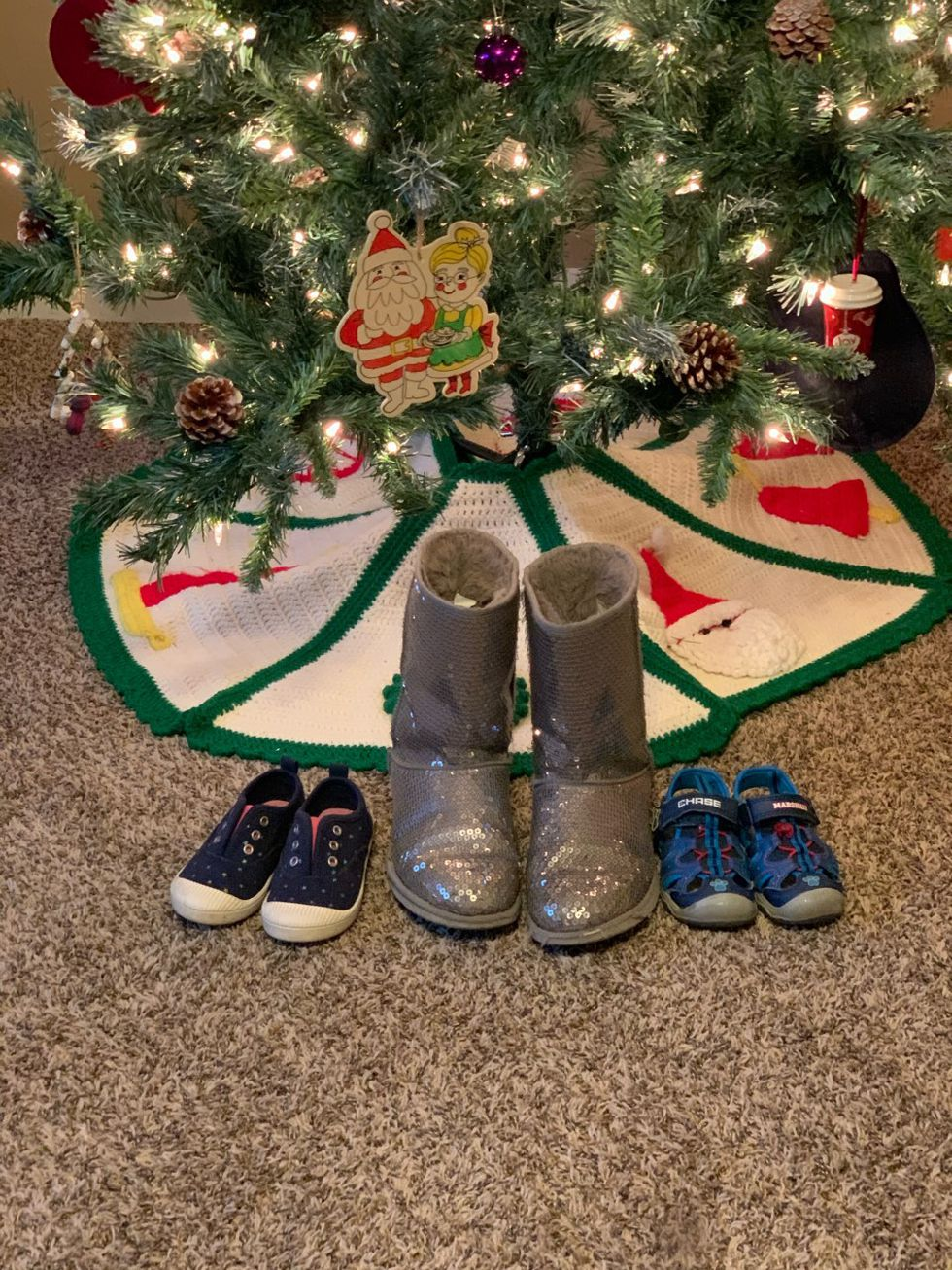 Children's shoes placed under Christmas tree